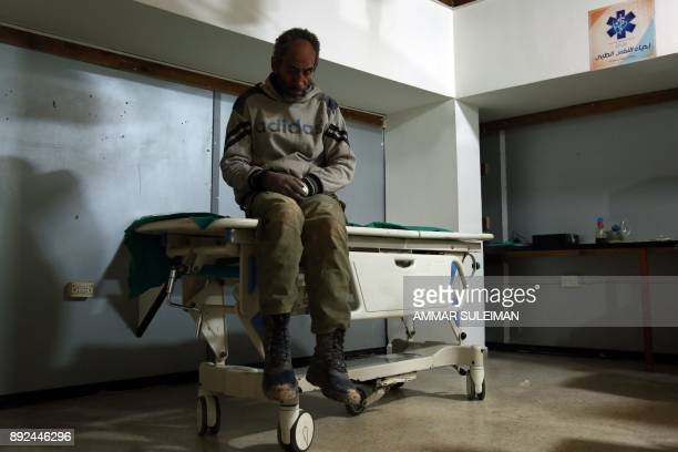 A Syrian man awaits treatment at a makeshift hospital in Zamalka near Syria's capital Damascus on December 14 following reported shelling / AFP PHOTO...