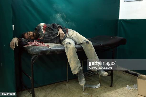 Syrian man awaits treatment at a makeshift hospital in Zamalka near Syria's capital Damascus on December 14 following reported shelling / AFP PHOTO /...