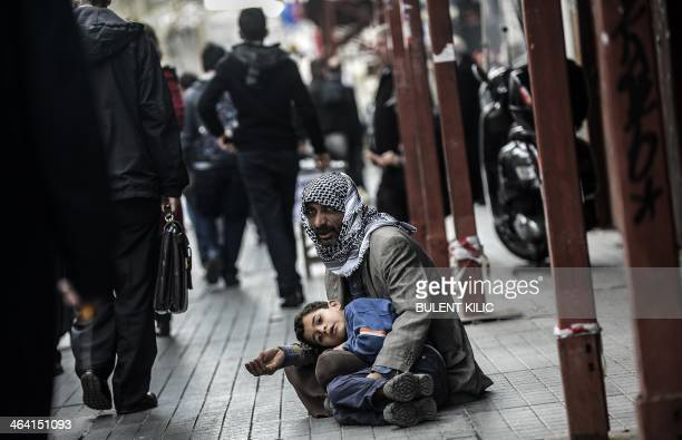 A Syrian man begs for money with a child at Istiklal Avenue on January 22 2014 in Istanbul The United Nations on January 20 2014 cancelled an...