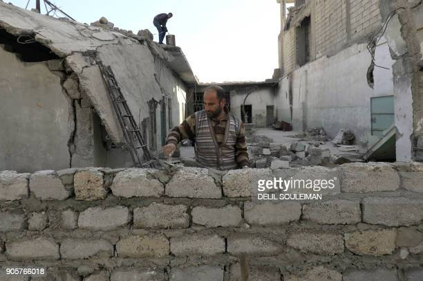 Syrian man builds a wall outside a heavily damaged building in the northern Syrian city of Raqa on January 11 2018 after a huge military operation...