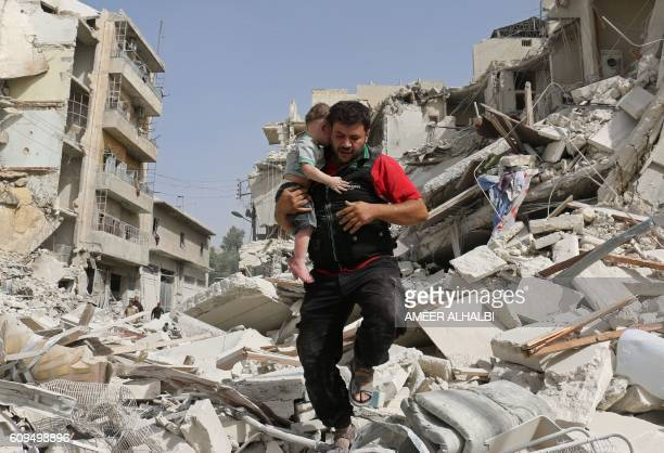 A Syrian man carries a baby after removing him from the rubble of a destroyed building following a reported air strike in the Qatarji neighbourhood...