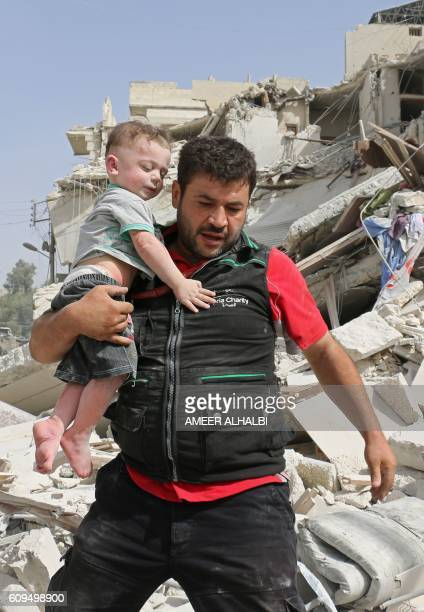 Syrian man carries a baby after removing him from the rubble of a destroyed building following a reported air strike in the Qatarji neighbourhood of...