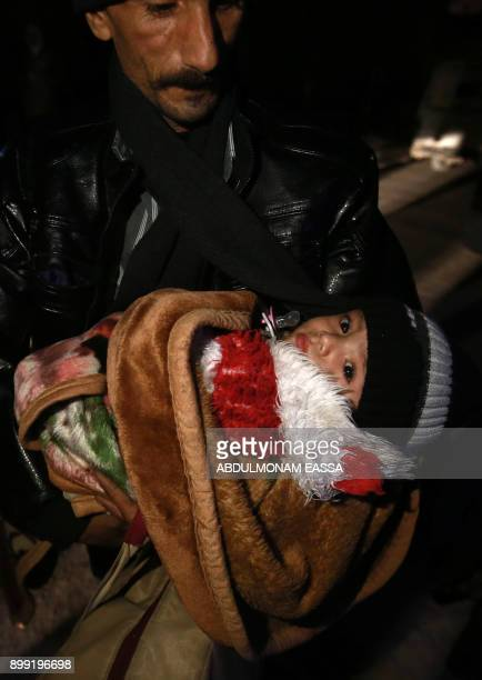 A Syrian man carries a baby on the second night of an evacuation operation led by the Syrian Red Crescent and the International Committee of the Red...