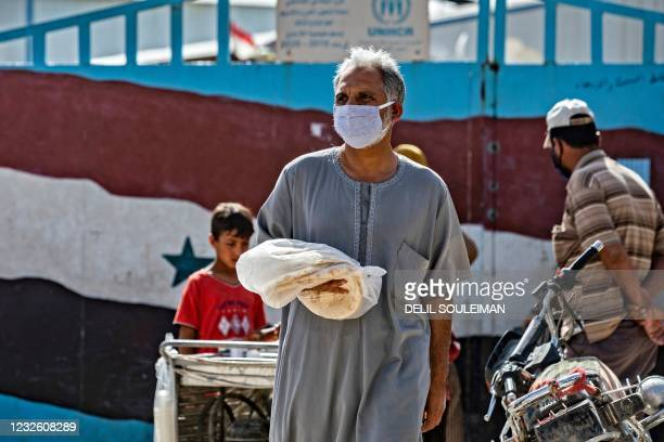 Syrian man carries a bag of bread at a market in Syria's northeastern city of Qamishli on April 30, 2021.