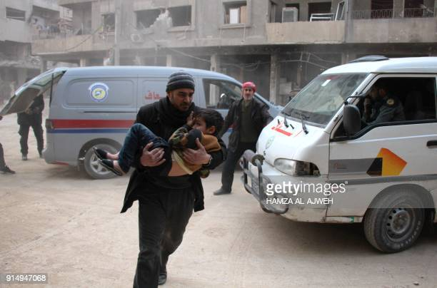 A Syrian man carries a boy who was injured in reported air strikes on the rebelheld besieged town of Douma in the eastern Ghouta region on the...
