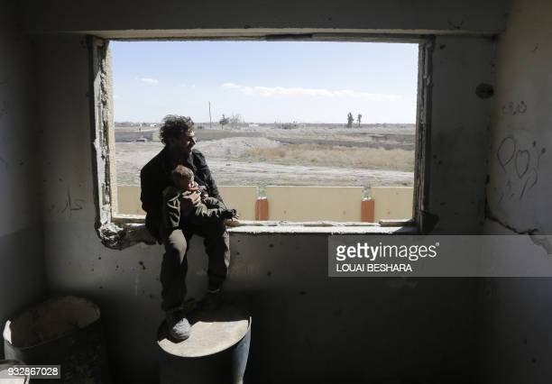 Syrian man carries a child after being evacuated from rebelheld areas in the Eastern Ghouta at a school in the regimecontrolled Hosh Nasri on the...