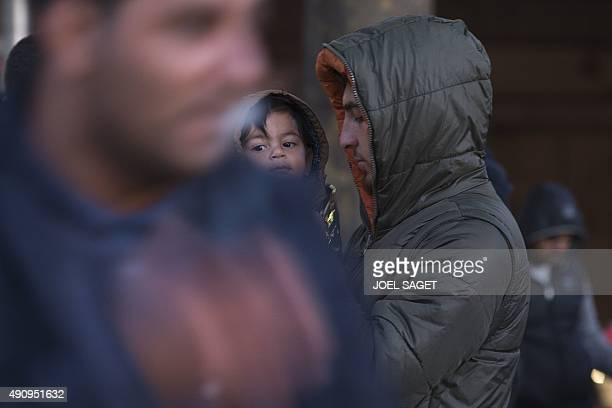 A Syrian man carries a child as he and other migrants and refugees are evicted by the French authorities from a camp at the Porte de SaintOuen in...