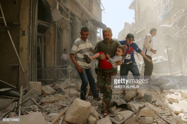 A Syrian man carries a child as they evacuate an area following a reported airstrike on April 22 2016 in the rebelheld neighbourhood of Hayy Aqyul in...