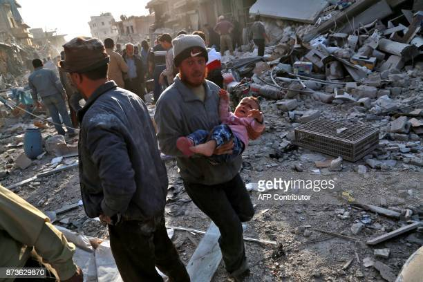 Syrian man carries a child following a reported airstrike on the rebelheld town of Atareb in Syria's northern Aleppo province on November 13 2017 At...