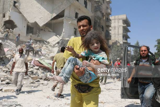 A Syrian man carries a child in the Maadi district of eastern Aleppo after regime aircrafts reportedly dropped explosivepacked barrel bombs on August...