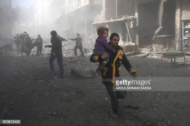 Syrian man carries a child injured in government bombing in the rebelheld town of Hamouria in the besieged Eastern Ghouta region on the outskirts of...