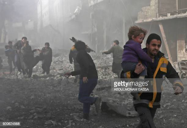 A Syrian man carries a child injured in government bombing in the rebelheld town of Hamouria in the besieged Eastern Ghouta region on the outskirts...