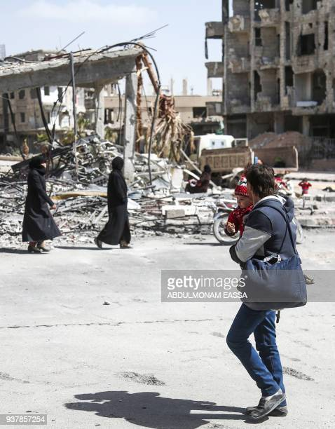 A Syrian man carries a child while walking during the evacuation from the town of Arbin in the Eastern Ghouta region on the outskirts of the capital...