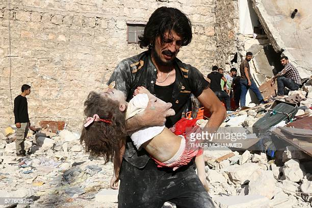 A Syrian man carries a child who was retrieved under the rubble of a collapsed building following a reported air strike on the rebelheld...