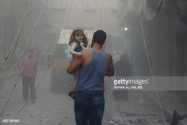 A Syrian man carries a girl on a street covered with dust following a air strike by government forces in the northern city of Aleppo on July 15 2014...