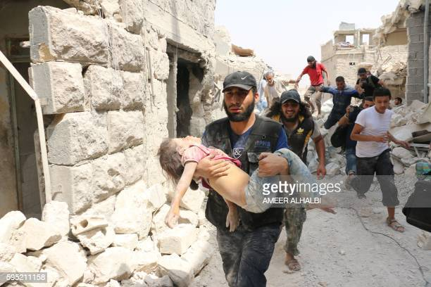 A Syrian man carries a wounded child following a barrel bomb attack on the Bab alNairab neighbourhood of the northern Syrian city of Aleppo on August...