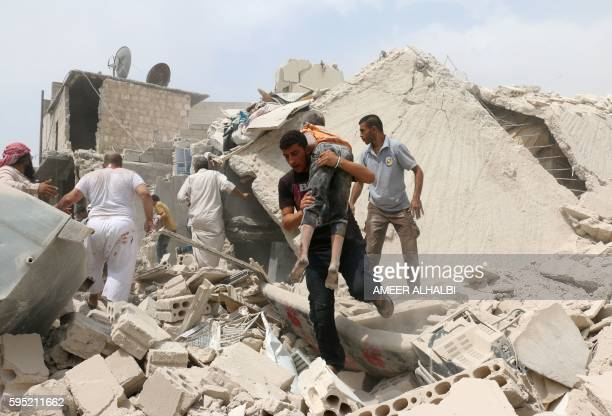 A Syrian man carries a wounded child in the rubble of buildings following a barrel bomb attack on the Bab alNairab neighbourhood of the northern...