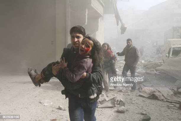 Syrian man carries a wounded girl after war crafts belonging to Assad Regime carried out airstrikes in the deescalation zone of Hamouriyah in...