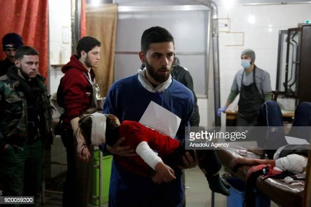Syrian man carries a wounded kid at a field hospital after war planes belonging to Assad Regime carried out airstrikes at the residential areas of...
