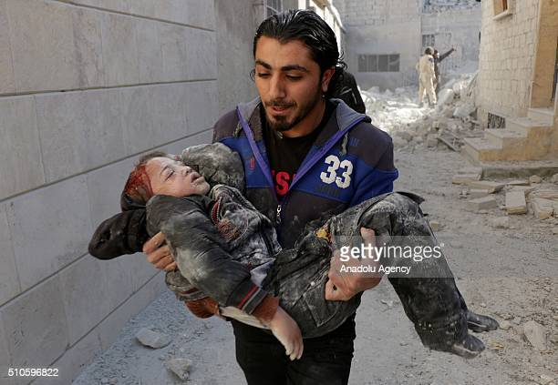 Syrian man carries a wounded kid, removed under the debris after Russian airstrikes targeted residential areas at Sahur neighborhood in Aleppo, Syria...