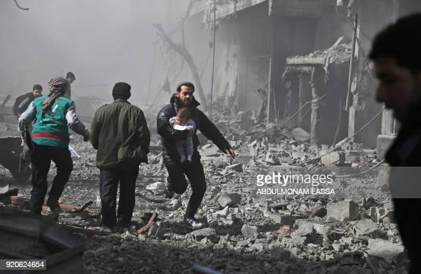 A Syrian man carries an infant injured in government bombing in the rebelheld town of Hamouria in the besieged Eastern Ghouta region on the outskirts...