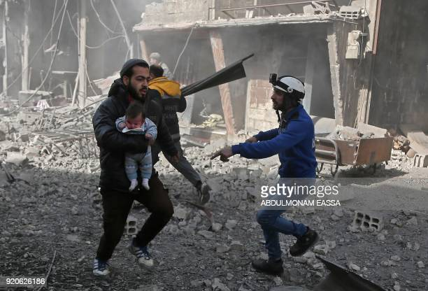 Syrian man carries an infant injured in government bombing in the rebelheld town of Hamouria in the besieged Eastern Ghouta region on the outskirts...