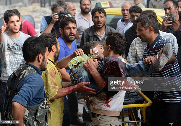 A Syrian man carries an injured child outside a hospital following shelling by Syrian government forces during battle with rebel fighters in the...