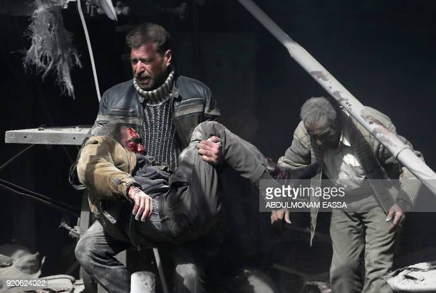 Syrian man carries an injured victim amid the rubble of buildings following government bombing in the rebel-held town of Hamouria, in the besieged...