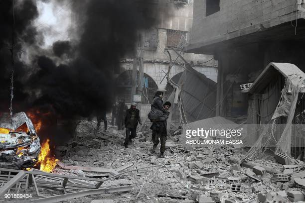 A Syrian man carries an injured woman following reported bombardment by Syrian and Russian forces in the rebelheld town of Hamouria in the Eastern...