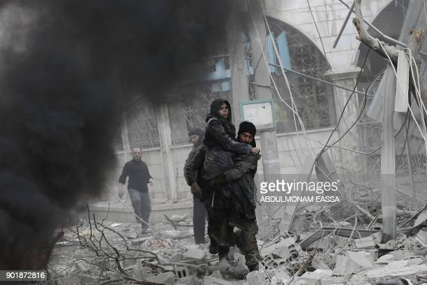 Syrian man carries an injured woman following reported bombardment by Syrian and Russian forces in the rebelheld town of Hamouria in the Eastern...