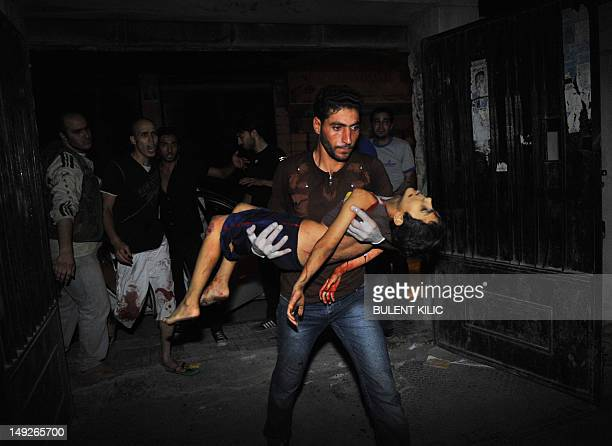 A Syrian man carries badly wounded fiveyearold Mohammed Amumrej after he was hurt during shelling by Syrian government forces in the center of...