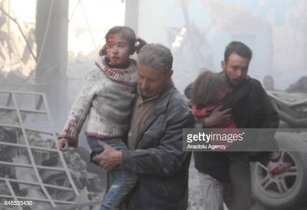 Syrian man carries her wounded daughter after Assad Regime's airstrike over civilians in residential areas at the Douma town of Eastern Goutha in...