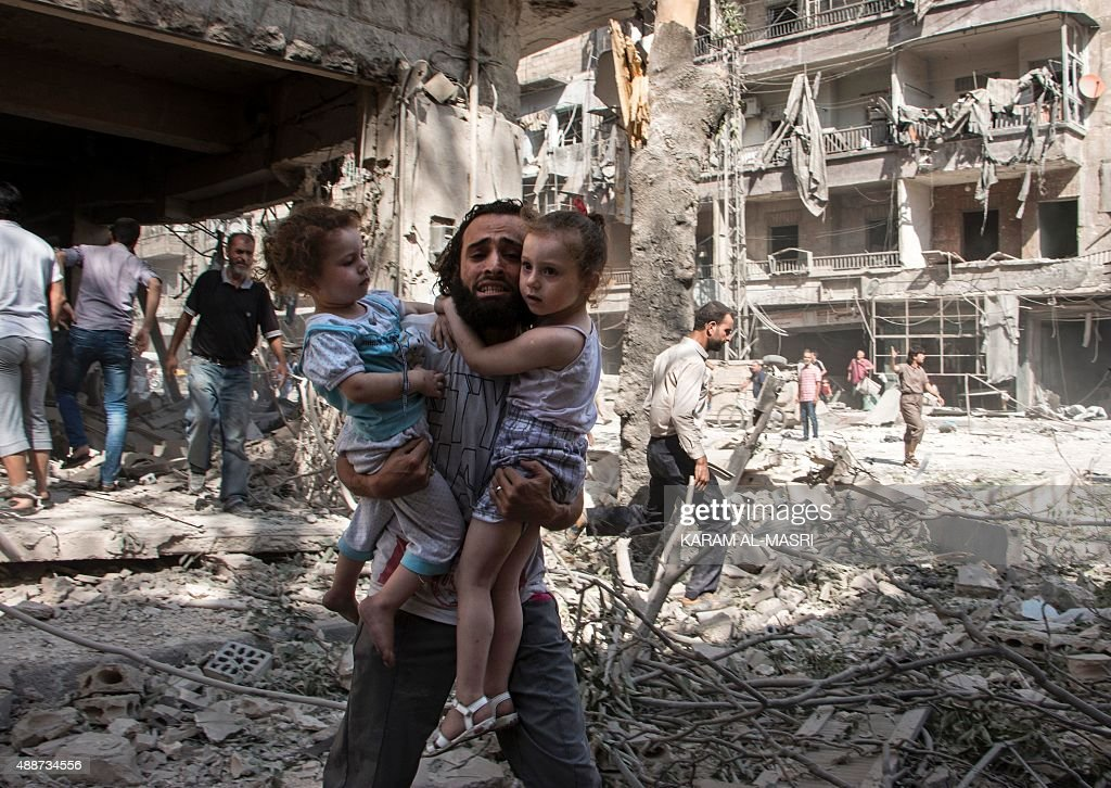 A Syrian man carries his two girls as he walks across the rubble following a barrel bomb attack on the rebel-held neighbourhood of al-Kalasa in the northern Syrian city of Aleppo on September 17, 2015. Once Syria's economic powerhouse, Aleppo has been ravaged by fighting since the rebels seized the east of the city in 2012, confining government forces to the west.