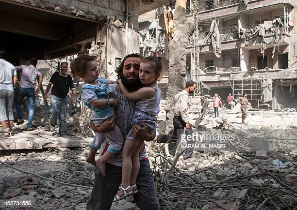 A Syrian man carries his two girls as he walks across the rubble following a barrel bomb attack on the rebelheld neighbourhood of alKalasa in the...