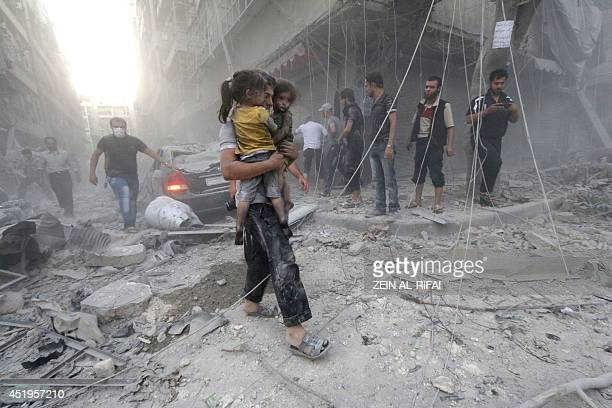 A Syrian man carries two girls covered with dust following a reported air strike by government forces on July 9 2014 in the northern city of Aleppo...