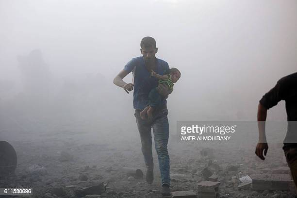 Syrian man carrying a child emerges from a dust cloud following a reported airstrike on Kafr Batna in the rebelheld Eastern Ghouta area on the...