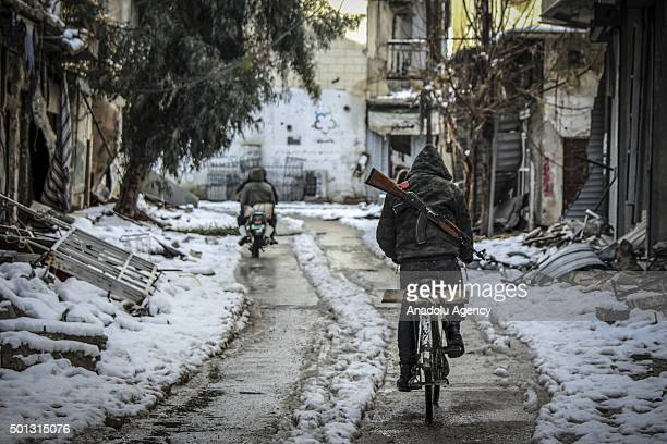 A Syrian man carrying an AK47 rides a bike in the snow on January 7 2015 in Jobar town of Damascus Syria
