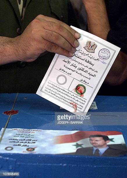 A Syrian man casts his vote stamped with blood from his finger in the 'yes' circle to endorse Bashar alAssad as the new Syrian president at a polling...