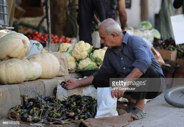 A Syrian man chooses aubergines at a street shop in Douma a rebelheld town on the outskirts of the capital Damascus on October 24 2017 According to...