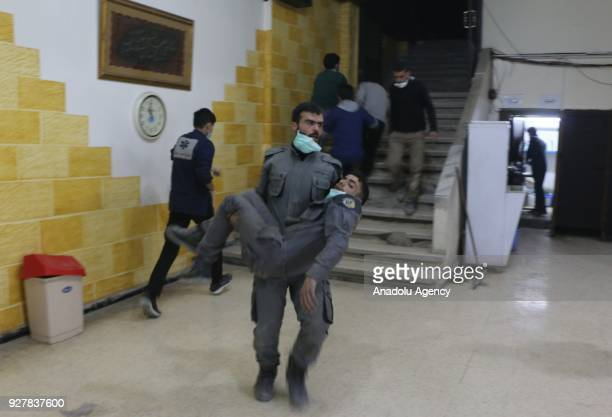 Syrian man civil defense team member carries a man affected by chemical gas at the field hospital after Assad Regime's alleged chlorine gas attack in...