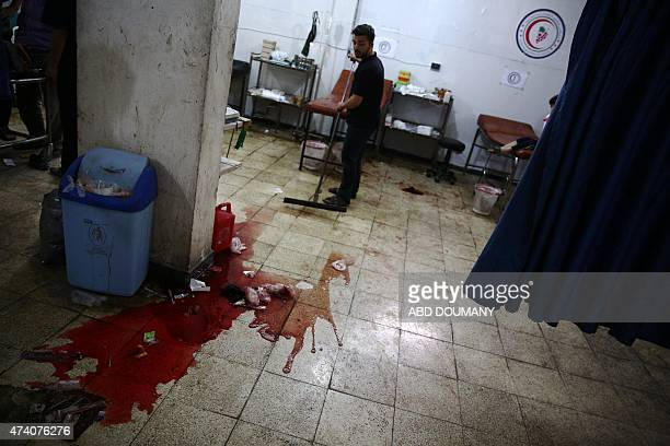 A Syrian man cleans the floor at a makeshift hospital in the rebelheld area of Douma east of the Syrian capital Damascus following reported air...