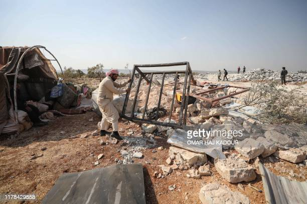 Syrian man clears debris at the site of helicopter gunfire which reportedly killed nine people near the northwestern Syrian village of Barisha in the...