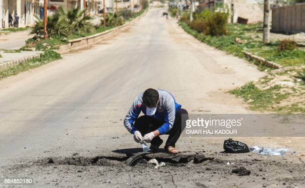 A Syrian man collects samples from the site of a suspected toxic gas attack in Khan Sheikhun in Syrias northwestern Idlib province on April 5 2017...
