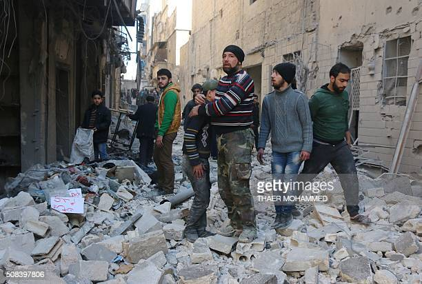 Syrian man comforts a boy amid the rubble of buildings following a reported air strike on the rebelheld neighbourhood of alKalasa in the northern...