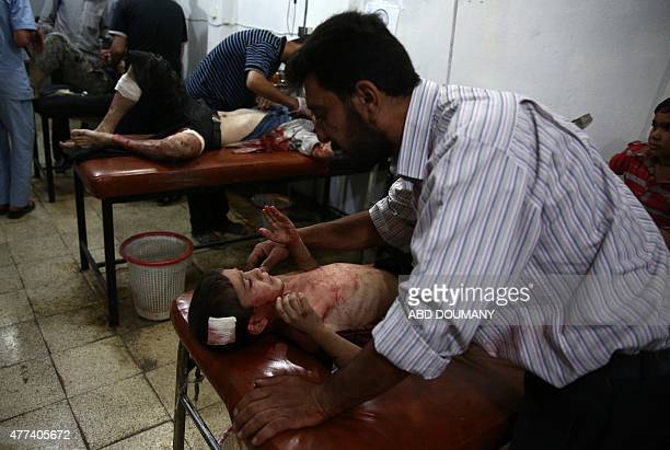 A Syrian man comforts a child as wounded Syrians wait for treatment at the Unified Medical Office for Douma a makeshift medical centre in the...