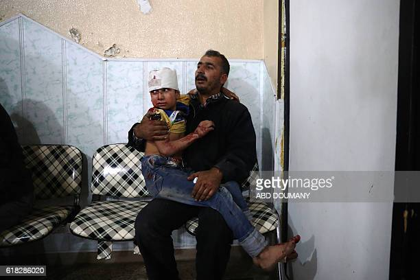 Syrian man comforts a wounded child at a makeshift hospital following reported government shelling on the rebelheld town of Douma east of the Syrian...
