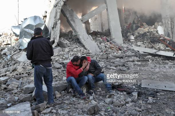 Syrian man comforts another on the rubble of a building after a reported Russian airstrike on a popular market in the village of Balyun in Syria's...
