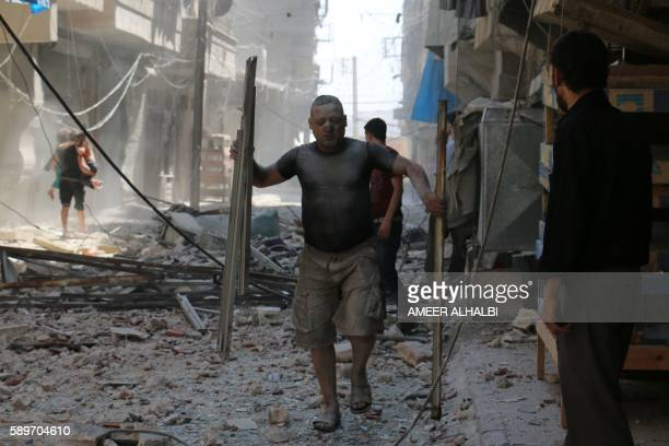 Syrian man covered with dust carries pieces of metal on a street cluttered with rubble following a reported air strike on the rebelheld neighbourhood...