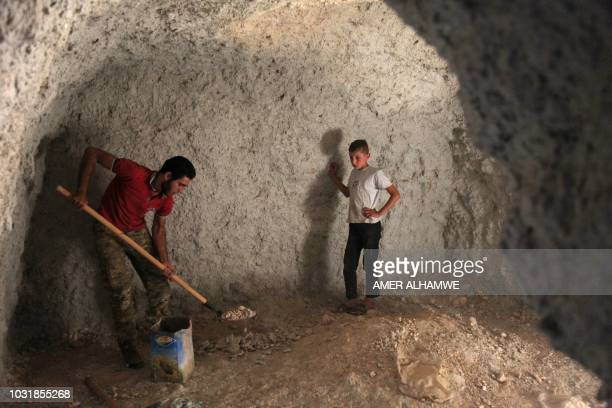 A Syrian man digs a cave with his brother at an unknown location in the southern countryside of Idlib province on September 11 in anticipation for an...