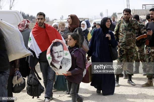 Syrian man draped in the national flag walks with another girl carrying a poster of President Bashar alAssad as they pass with other civilians...